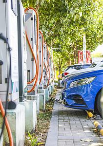 新能源汽车充电站充电桩和正在充电的汽车图片