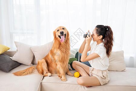 美女给宠物狗拍照图片