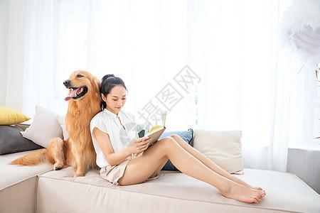 美女主人与宠物狗相伴看书图片