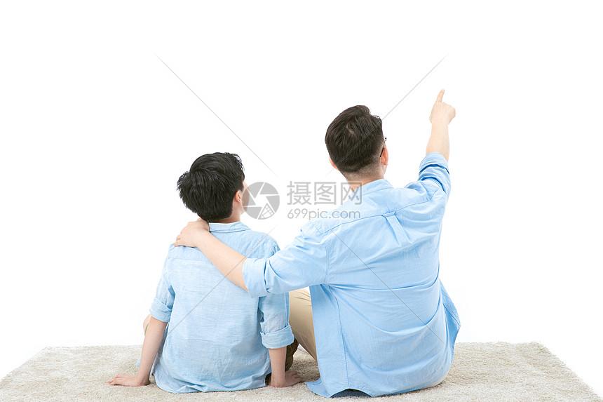 父子一起坐地毯上看远方图片