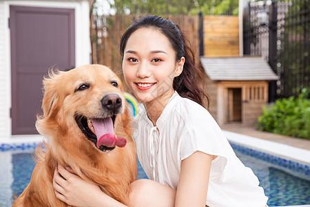 年轻美女主人与宠物金毛犬嬉戏图片
