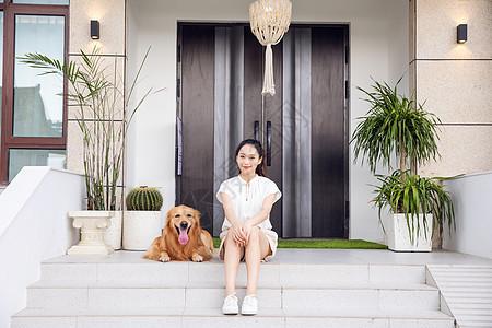 年轻美女与宠物狗门口嬉戏图片