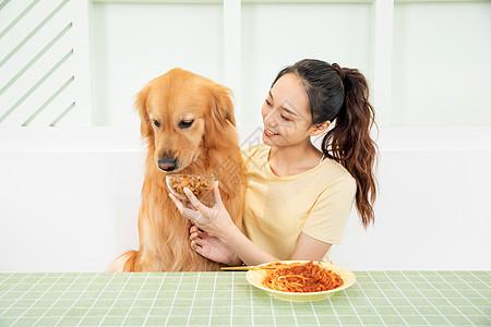美女主人和宠物狗一起吃饭图片