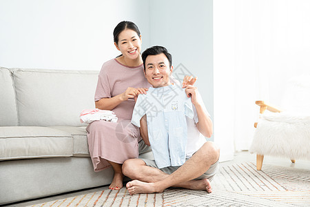 孕妇和丈夫在家收拾婴儿衣服图片