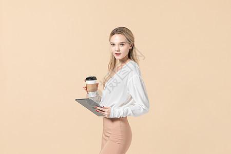 拿着平板电脑和咖啡杯的外国女模特图片