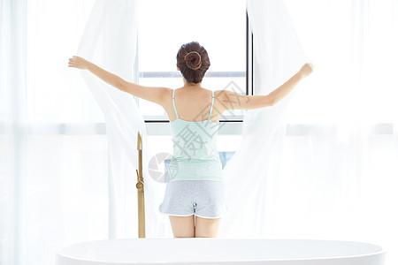 年轻女性拉开窗帘图片