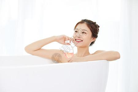 美女躺在浴缸洗泡泡浴喝鸡尾酒图片