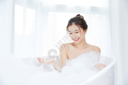 女性躺在浴缸里洗泡泡浴图片