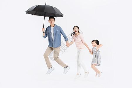 一家三口撑伞跳跃图片