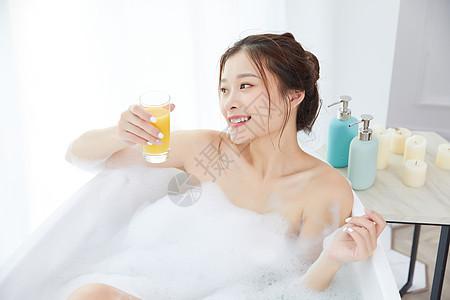美女洗泡泡浴喝着橙汁图片