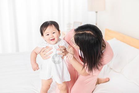妈妈扶着宝宝在床上走路图片