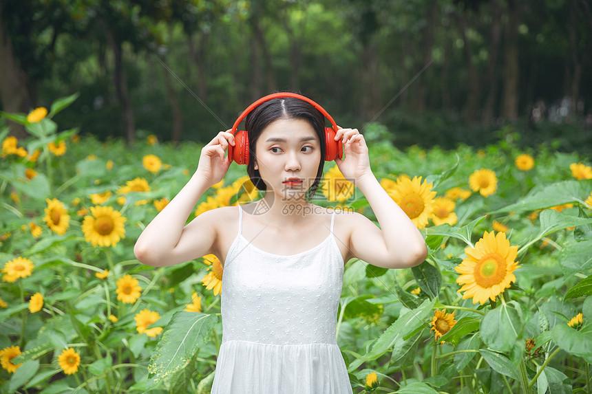 向日葵中戴耳机的少女图片