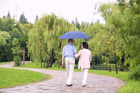 老年夫妇在公园雨中漫步背影图片