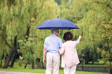 老年夫妇雨中散步背影图片