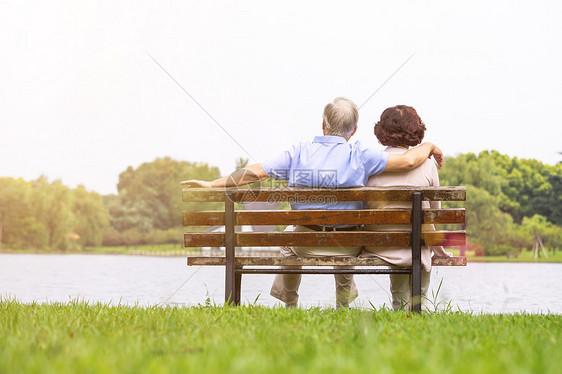 老年夫妇坐在公园长椅背影图片