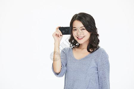 年轻美女拿卡片相机拍照图片