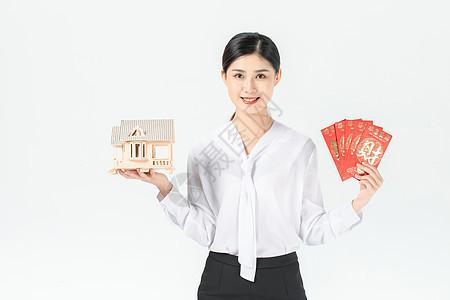 商务女性手捧房子和红包图片