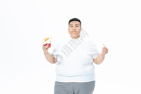 青年肥胖男性吃汉堡和薯条图片