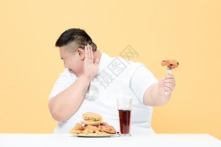 青年肥胖男性拒绝炸鸡图片