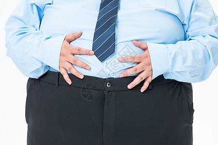 肥胖商务男性摸着肚子图片