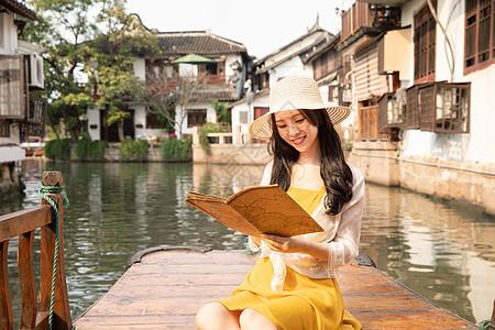 年轻美女乘船郊游看地图图片