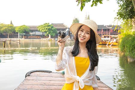年轻美女乘船郊游拍照图片