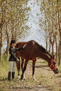 青年女性户外牵马图片