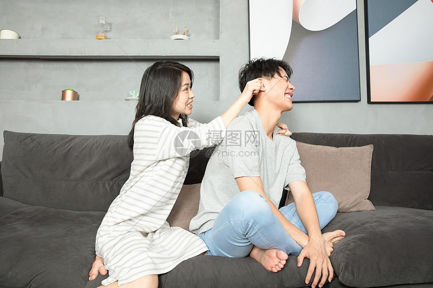 可爱夫妻沙发上嬉戏打闹图片