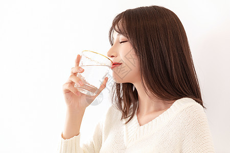 女性端着杯子喝水图片