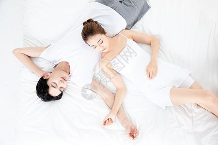 年轻情侣躺在床上睡觉图片