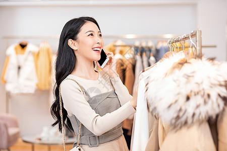 年轻美女逛街边打电话边购物挑选衣服图片