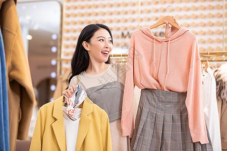 年轻美女逛街购物挑选衣服图片