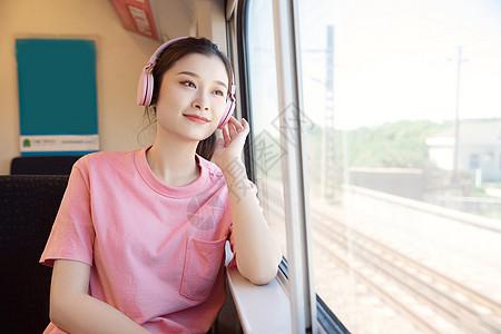 青年女性坐在高铁上听歌图片