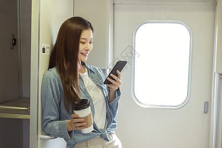 青年女性在车厢过道看手机图片