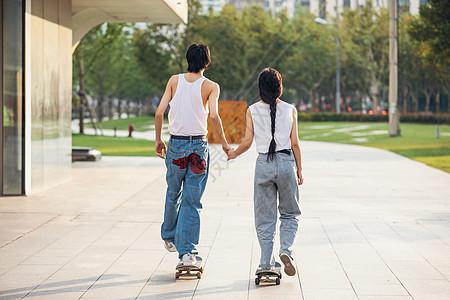 情侣户外玩滑板背影图片
