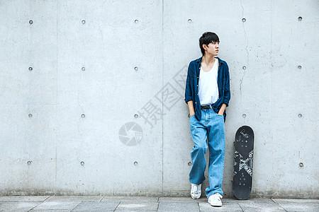 靠着墙的滑板男性 图片