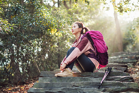 女生坐在山间小路上休息图片