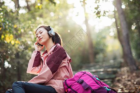 女生坐在山间小路上听音乐图片