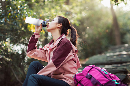 女生坐在山间小路上喝水图片