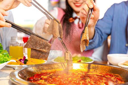 青年聚会吃火锅涮毛肚特写图片