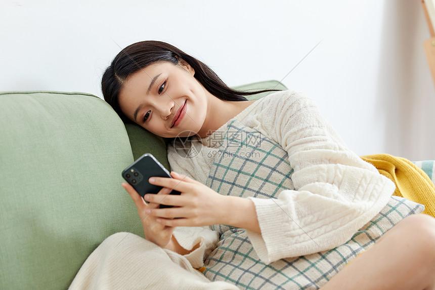 居家美女坐沙发玩手机图片