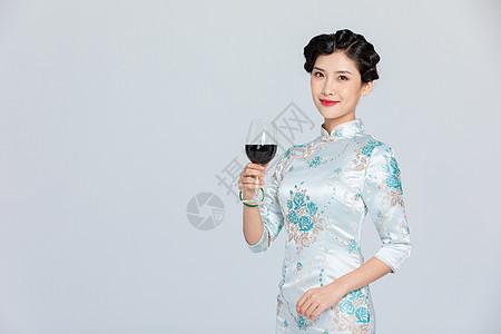 旗袍女性拿红酒图片