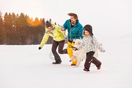 一家人和狗在雪地里奔跑图片