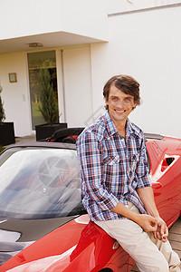 男人骄傲地坐在他的跑车上图片