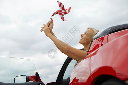 在电动汽车里拿风车的女孩图片