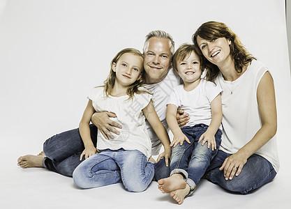 父母与儿子和女儿坐在地板上的工作室画像图片