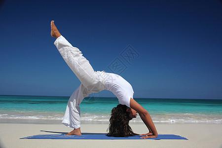 在海滩天堂岛拿骚巴哈马做瑜伽的年轻女子图片