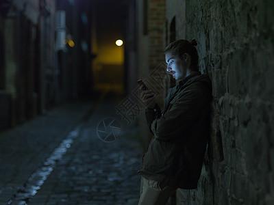 年轻人在街上晚上靠在墙上用智能手机图片