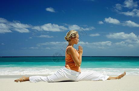 在热带海滩上练习瑜伽的女人图片