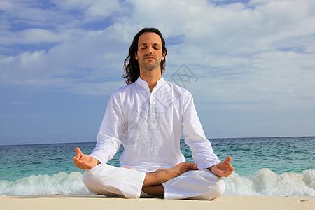 在热带海滩上冥想的人图片